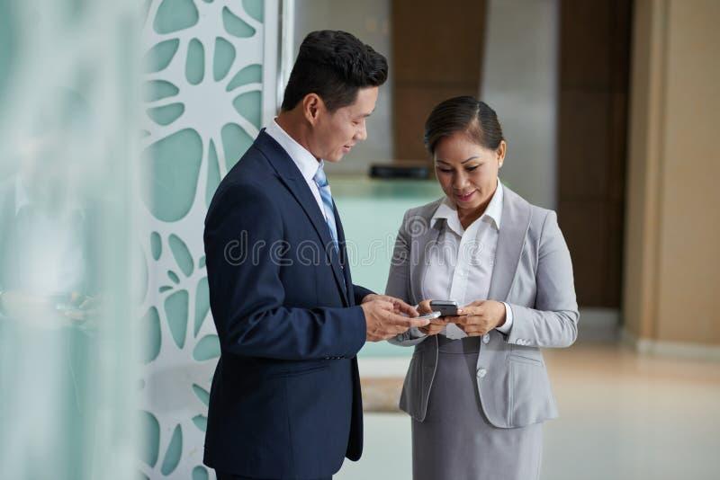 Associés échangeant des numéros de téléphone photos libres de droits