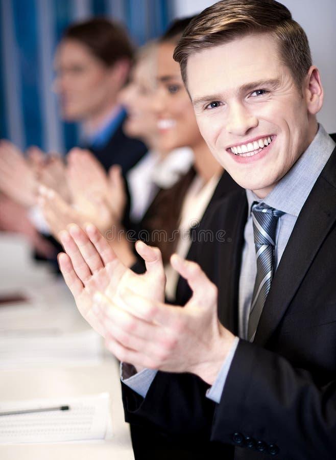 Associés applaudissant, foyer sur le type photographie stock libre de droits