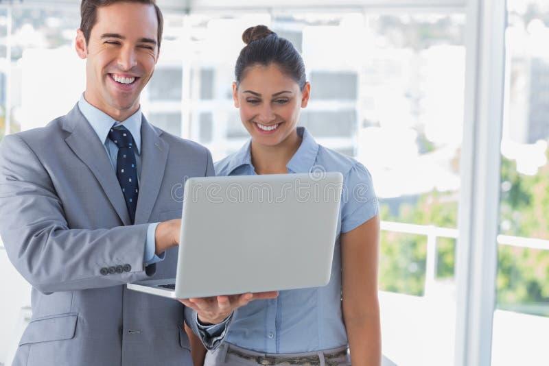 Associés d'homme d'affaires regardant l'ordinateur portable et rire photo stock
