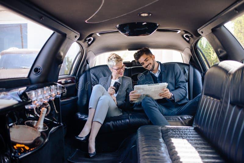 Associés dans la limousine regardant le journal image stock