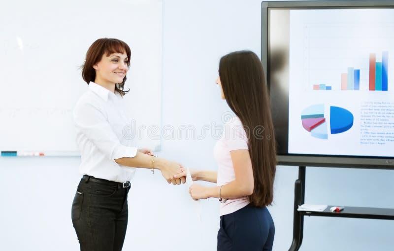 Associés - la femme se serrent la main après une présentation réussie au programme croissant de vone photographie stock