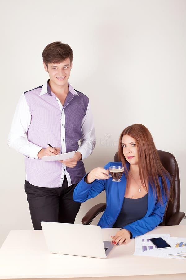 Associés occasionnels travaillant ensemble sur l'ordinateur portable au bureau dans le bureau créatif image stock