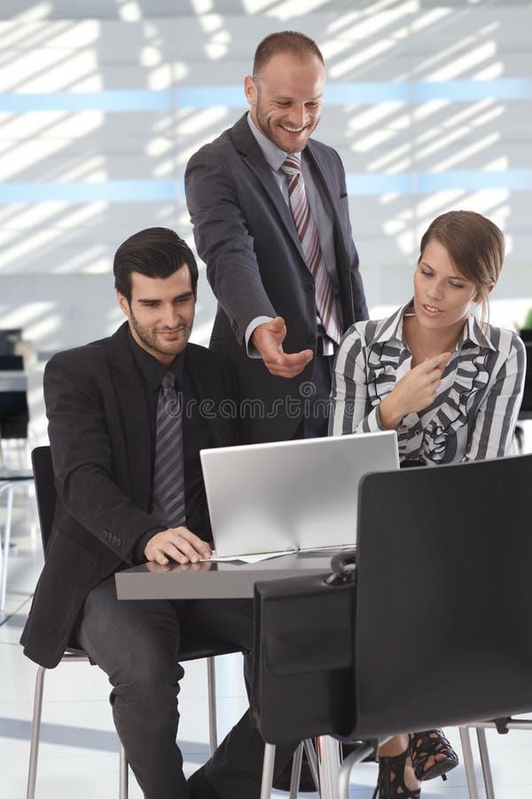 Associés parlant au-dessus de l'ordinateur portable dans le lobby images libres de droits