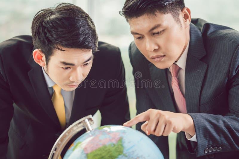 Associés regardant le globe photographie stock