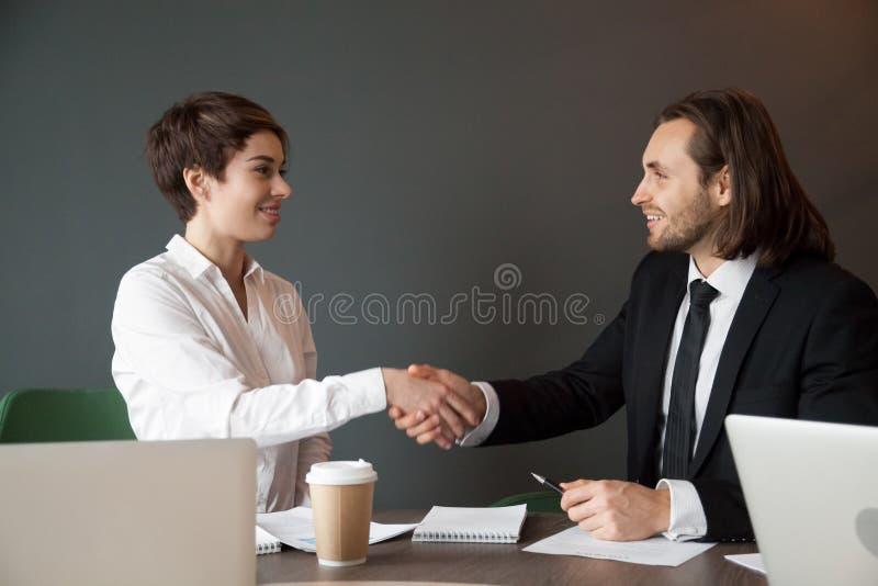 Associés saluant avec la poignée de main au cours de la réunion de bureau photo stock