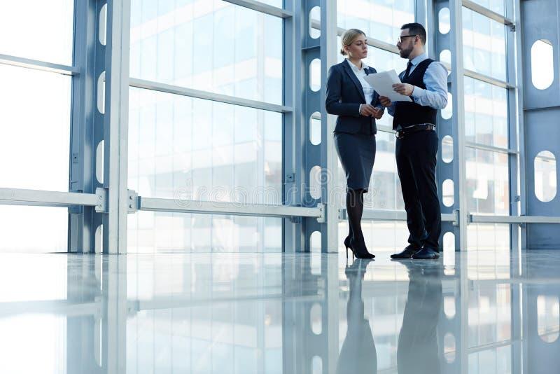 Associés se réunissant dans Hall de verre moderne image stock