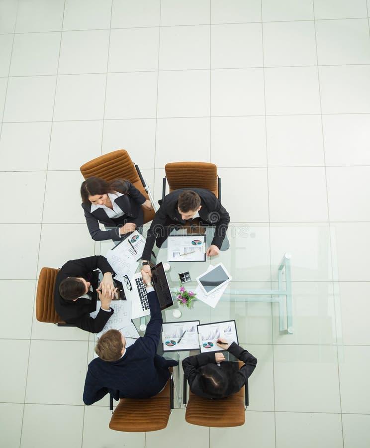 associés se serrant la main après un examen du nouveau Traité fiscal photographie stock libre de droits