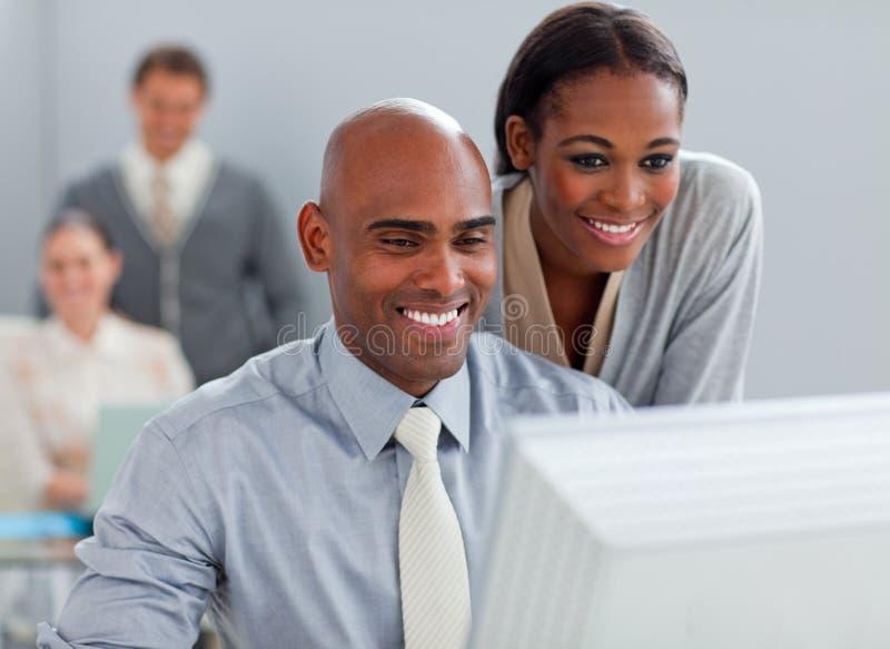 Associés travaillant à un ordinateur ensemble photos stock