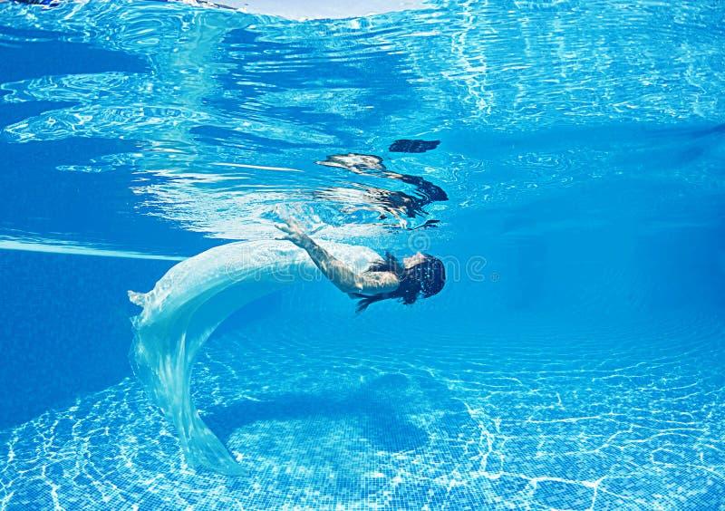 Associação azul do dia ensolarado da nadada subaquática branca bonita do mergulho do vestido da menina da mulher fotografia de stock