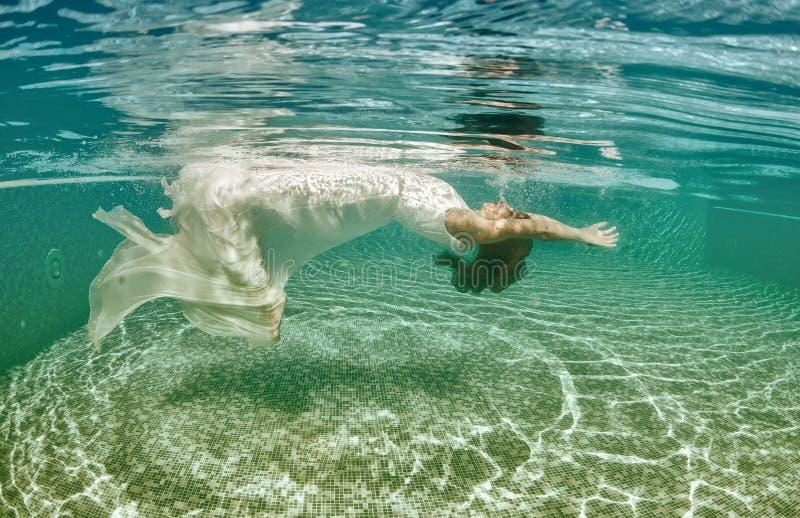 Associação azul do dia ensolarado da nadada subaquática branca bonita do mergulho do vestido da menina da mulher imagem de stock