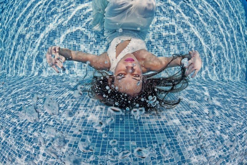 Associação azul do dia ensolarado da nadada subaquática branca bonita do mergulho do vestido da menina da mulher fotos de stock royalty free