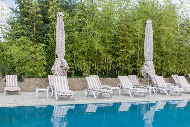 A associação com agua potável, camas do sol, dobrou barracas, bambu foto de stock royalty free