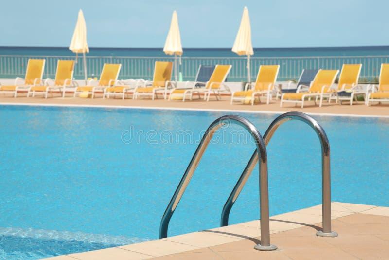 Associação de Uswimming com escada, salas de estar e guarda-chuvas fotos de stock