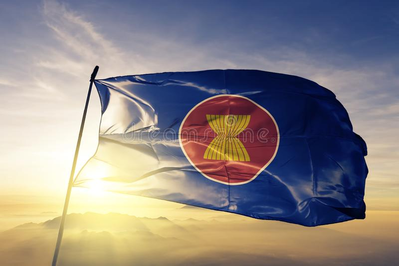 Association of Southeast Asian Nations ASEAN flag textile cloth fabric waving on the top sunrise mist fog. Beautiful royalty free illustration