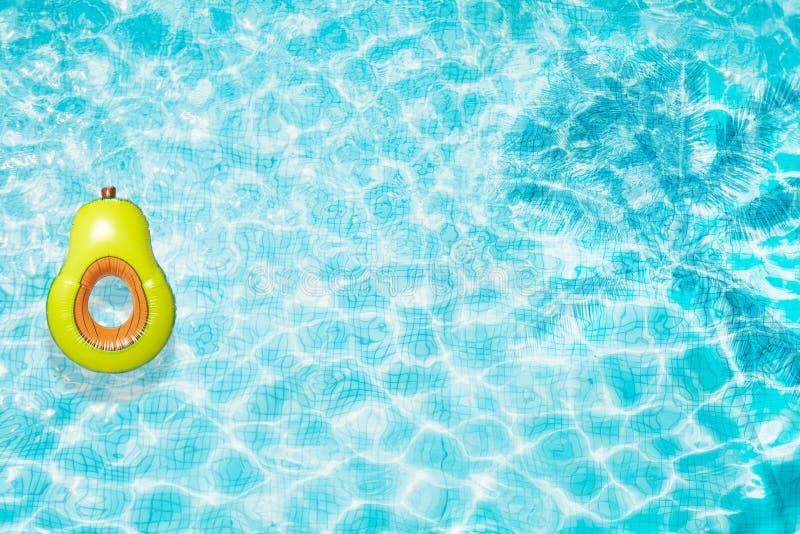 Associe o flutuador, anel que flutua em uma piscina azul de refrescamento com sombras da folha da palmeira na água imagens de stock