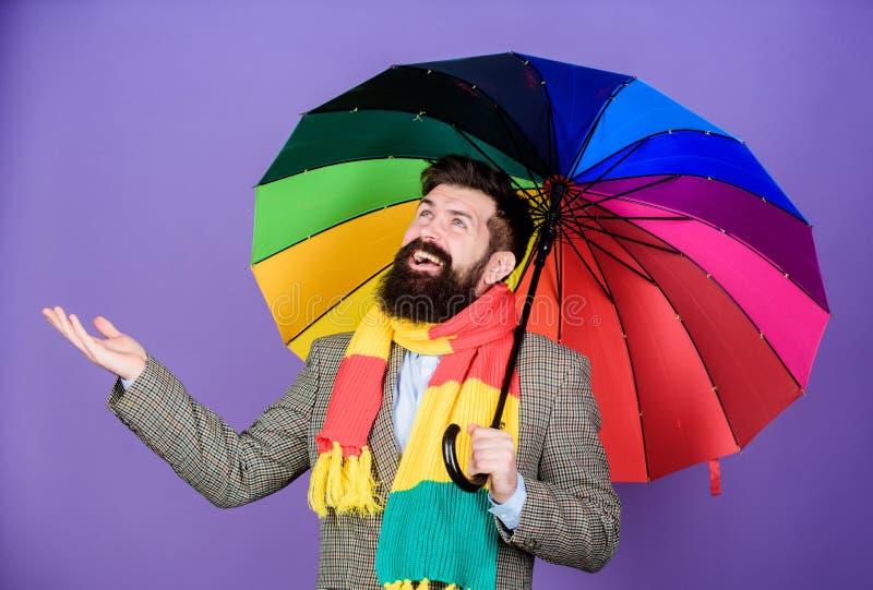 Assomigliando a suo andare piovere autism Uomo autistico della pioggia che tiene ombrello variopinto Uomo barbuto che controlla s immagine stock