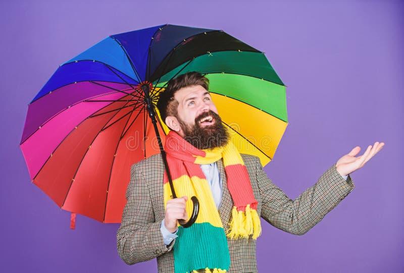Assomigliando a suo andare piovere autism Uomo autistico della pioggia che tiene ombrello variopinto Uomo barbuto che controlla s fotografia stock