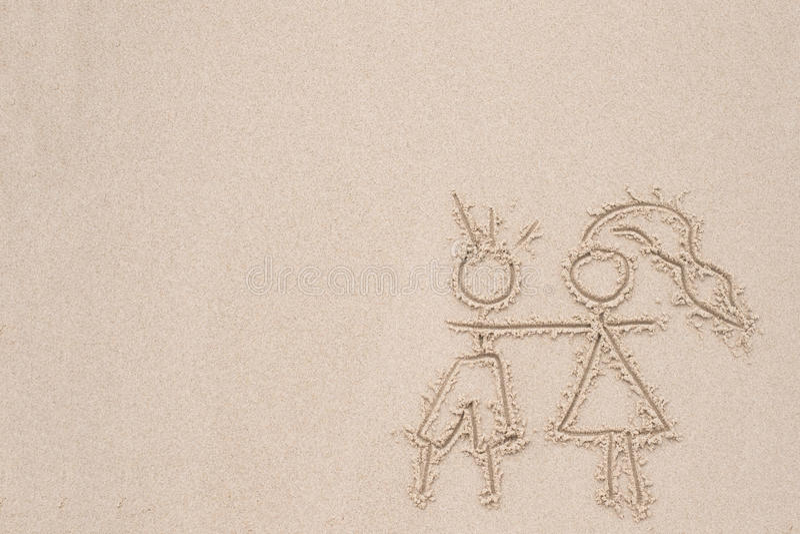 Assorbire la sabbia che descrive amore dell'uomo e della donna fotografie stock libere da diritti