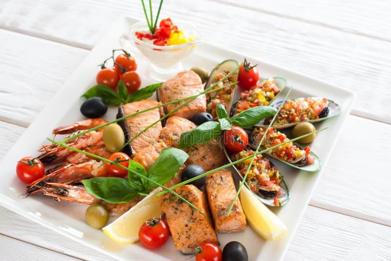 Assorted烤了在白色板材的海鲜用调味汁 免版税图库摄影