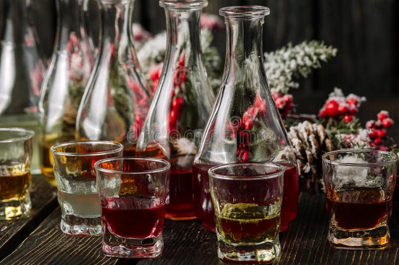 Assorted alcoholic cordials in glasses and decanters with Christmas decorations stock photos