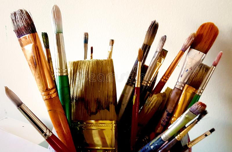 Assorted artist paint brushes for fine art painting. A colorful assortment of used artist's paint brushes in a can. Collection of thick and thin paint stock image