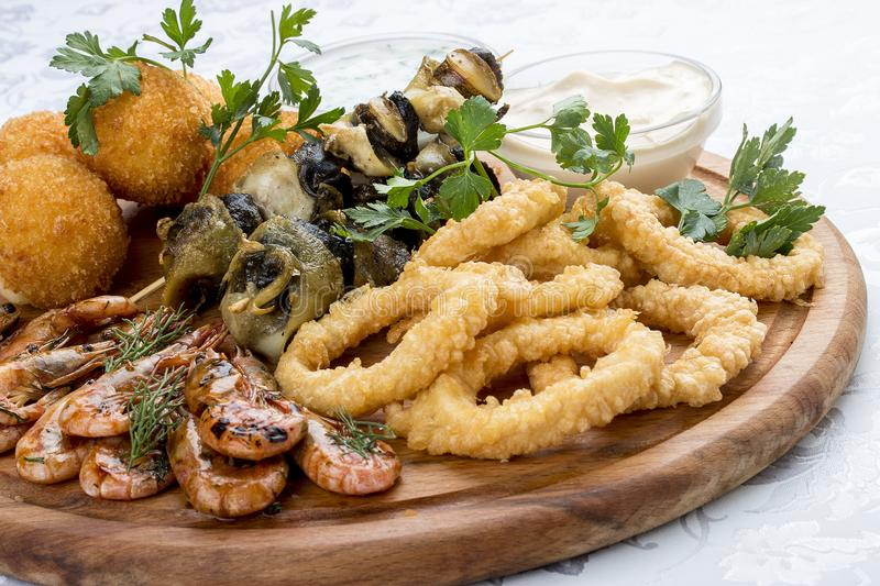 Assorted beer snacks. Cheese balls, mussels grill, shrimp, squid rings stock photo