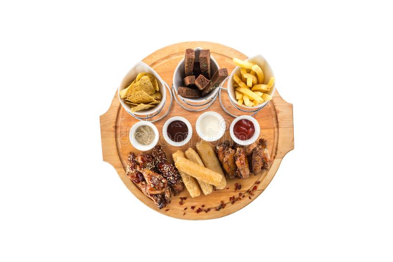 Assorted beer snacks like chicken wings, mozzarella sticks, croutons, nachos, french fries isolated on white background. Assorted beer snacks chicken wings stock photo
