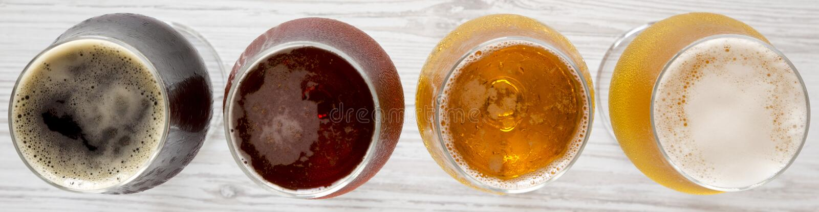 Assorted beers on a white wooden surface, top view. Overhead, from above.  royalty free stock image