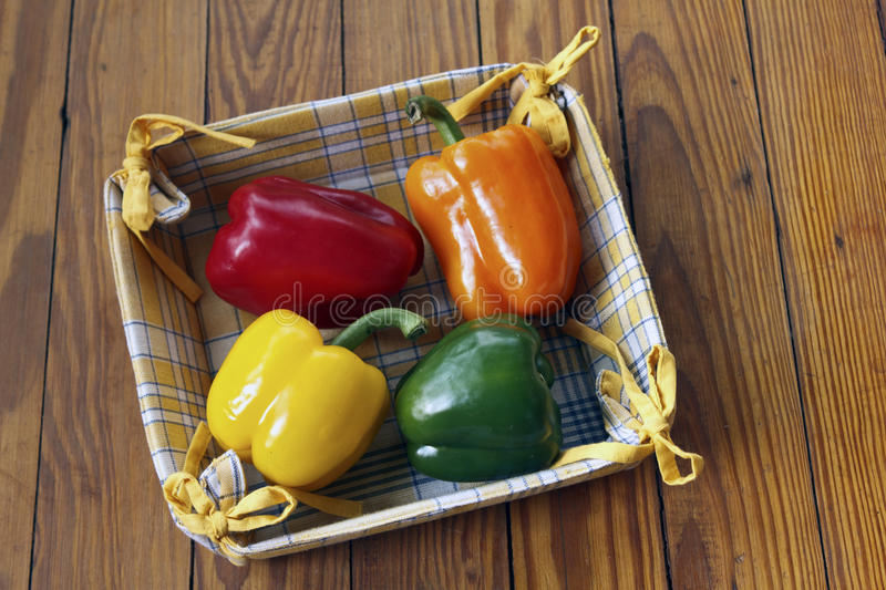 Assorted Bell Peppers. In red, green, orange, yellow in a cloth basket on a wooden table stock images