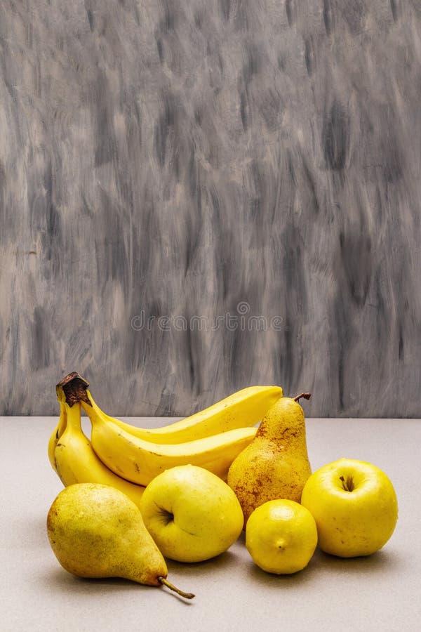Assorted bright yellow fruits. Fresh banana, pear, apple, lemon royalty free stock photo