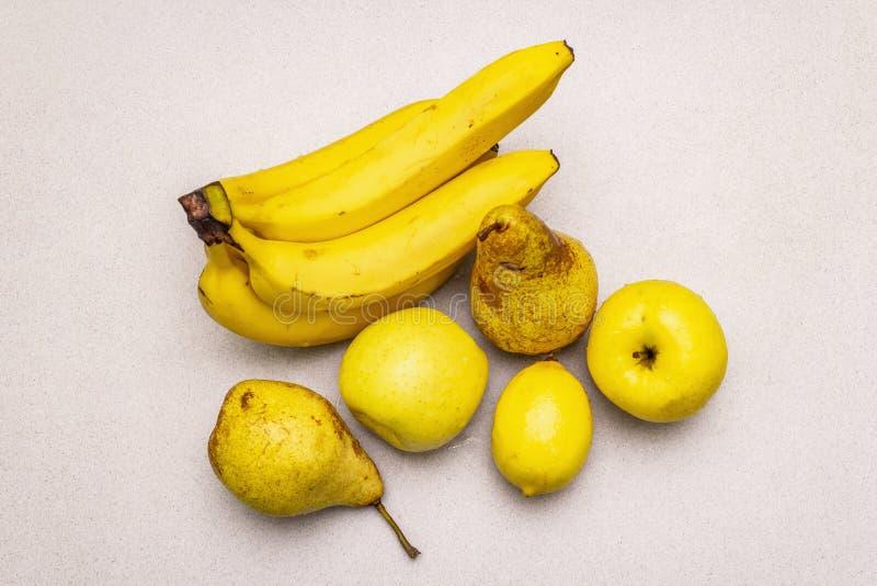 Assorted bright yellow fruits. Fresh banana, pear, apple, lemon. Harvest on a stone background royalty free stock photo