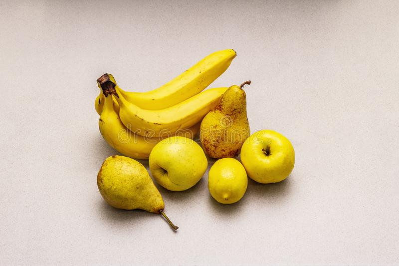 Assorted bright yellow fruits. Fresh banana, pear, apple, lemon. Harvest on a stone background royalty free stock images