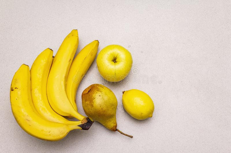 Assorted bright yellow fruits. Fresh banana, pear, apple, lemon. Harvest on a stone background royalty free stock photography