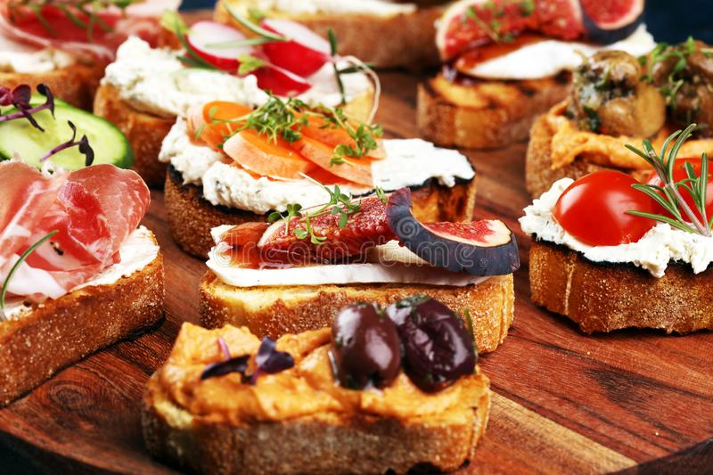 Assorted bruschetta with various toppings. Appetizing bruschetta or brie crostini. Variety of small sandwiches. Mix bruschetta on royalty free stock photography