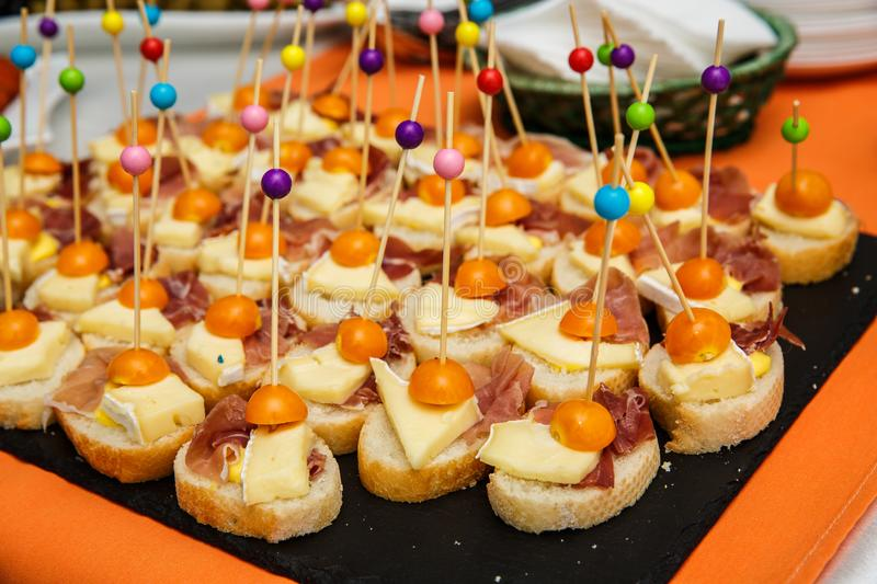 Assorted canapes on table closeup. Selection of tasty bruschetta on toasted baguette with prosciuto cheese tomato stock photos