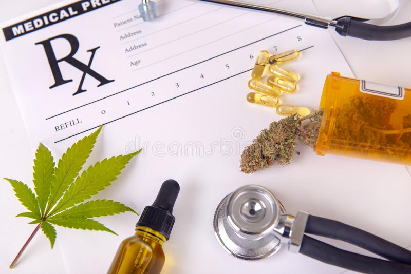 Assorted cannabis products, pills and cbd oil over medical prescription sheet royalty free stock images