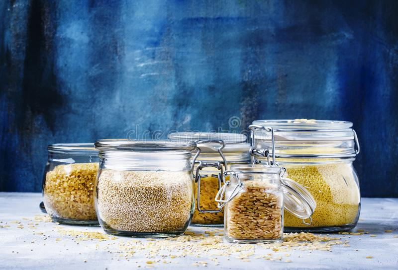 Assorted cereals in glass jars: kinoa, bulgur, couscous, orzo, b. Rown rice, selective focus stock images
