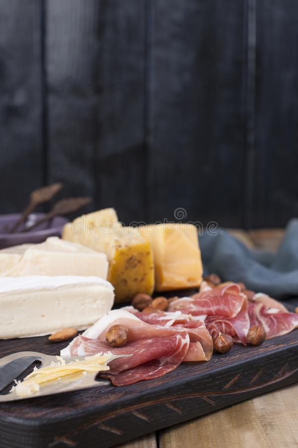 Assorted cheese, meat and olives. A delicious Italian snack for a party. Copy space.  royalty free stock photos