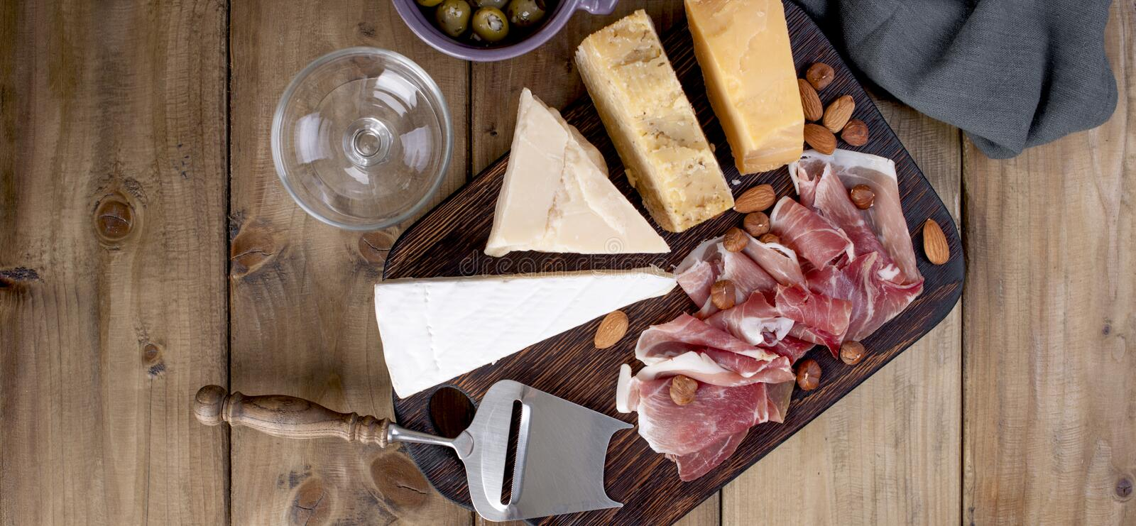 Assorted cheese, meat and olives. A delicious Italian snack for a party. Copy space . Banner.  stock image