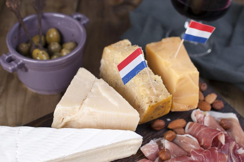 Assorted cheese, meat, wine in a glass and olives. Delicious Dutch snack for a party. View from above. Copy space.  stock image