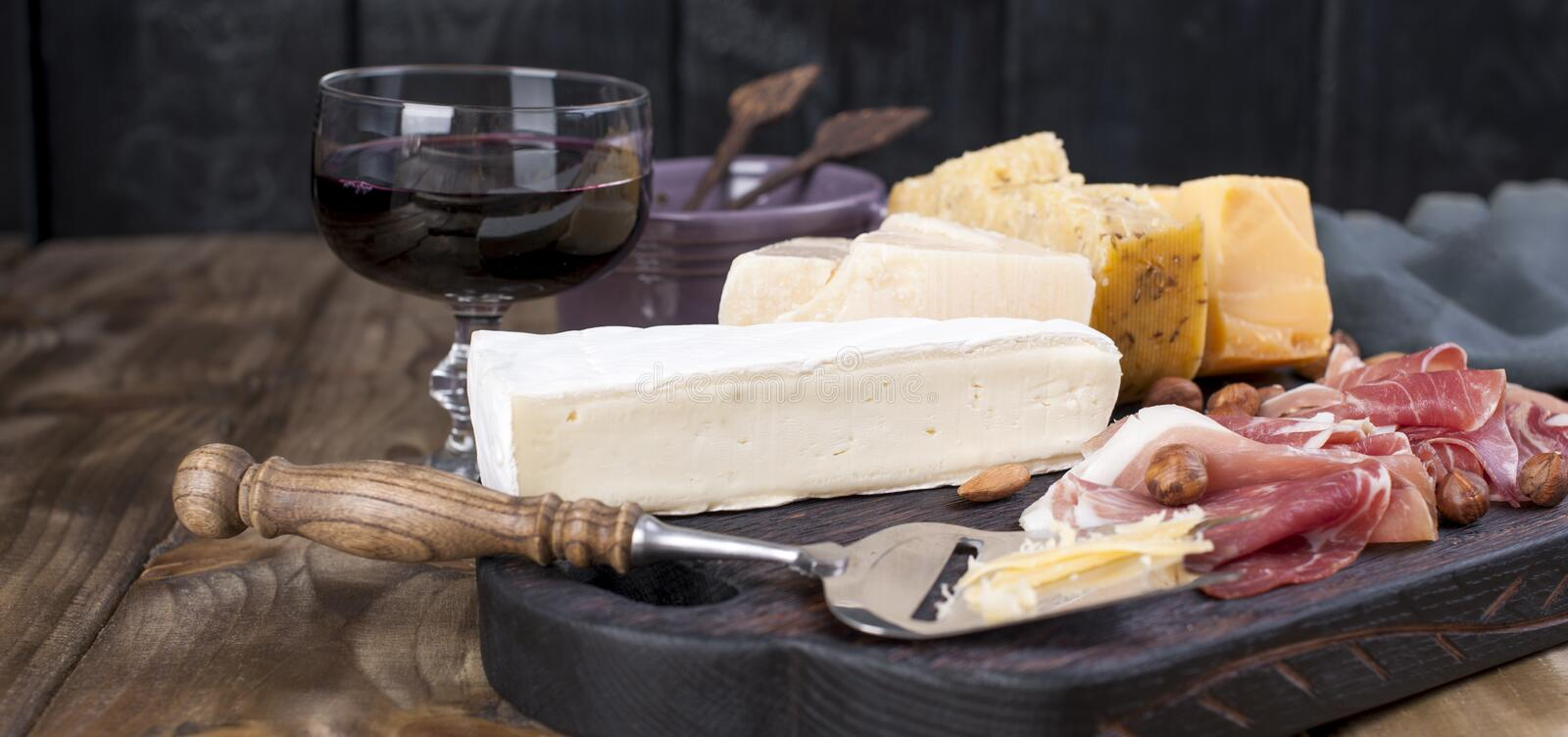 Assorted cheese, meat, wine in a glass and olives. A delicious Italian snack for a party. Copy space.  royalty free stock photo