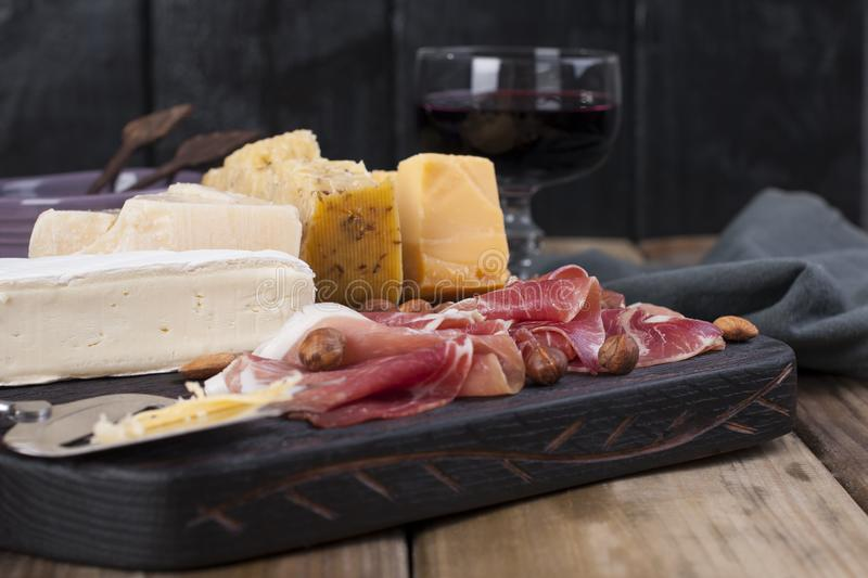 Assorted cheese, meat, wine in a glass and olives. A delicious Italian snack for a party. Copy space.  stock photos