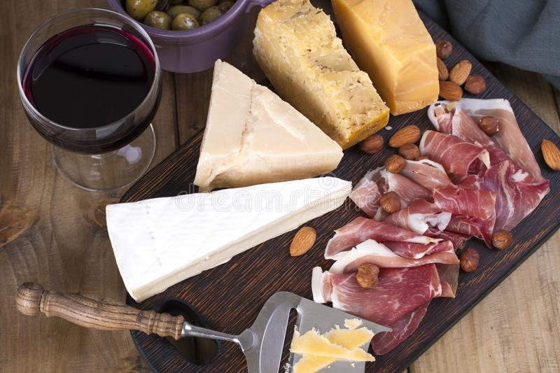 Assorted cheese, meat, wine in a glass and olives. A delicious Italian snack for a party. View from above. Copy space.  royalty free stock image