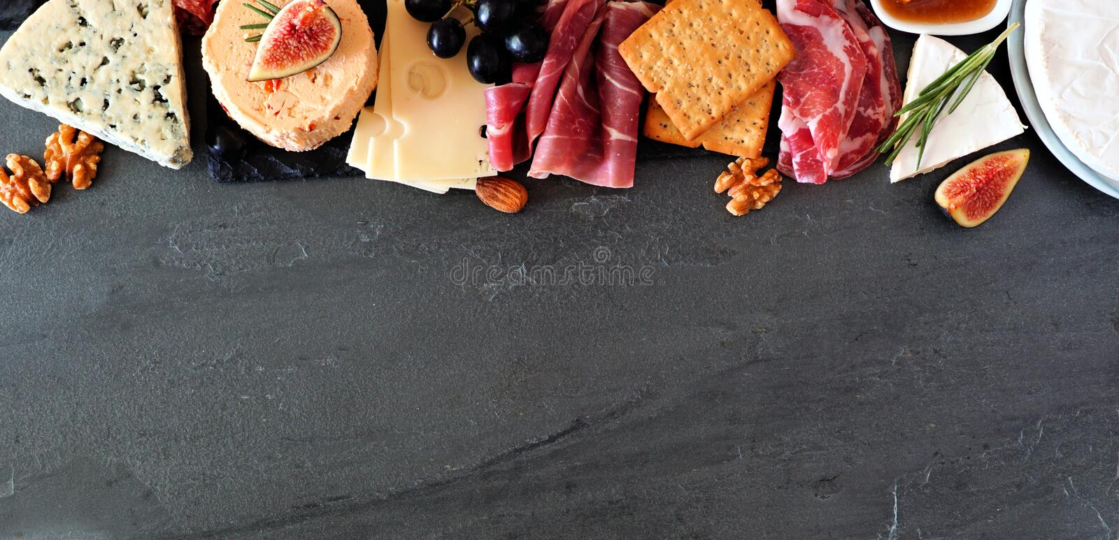 Assorted cheeses and meat appetizers, above view top border banner on a dark stone background with copy space royalty free stock images