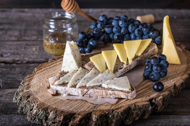 Assorted cheeses with grapes, bread, honey. Goat cheese. wooden board. Italian appetizer. bruschetta. Breakfast concept royalty free stock images