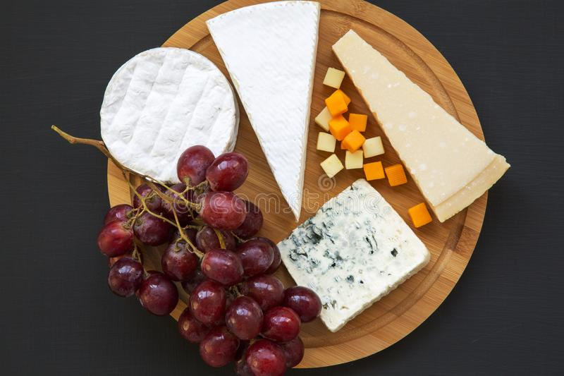 Assorted cheeses with grapes on round wooden board on dark background. Food for romantic. stock images