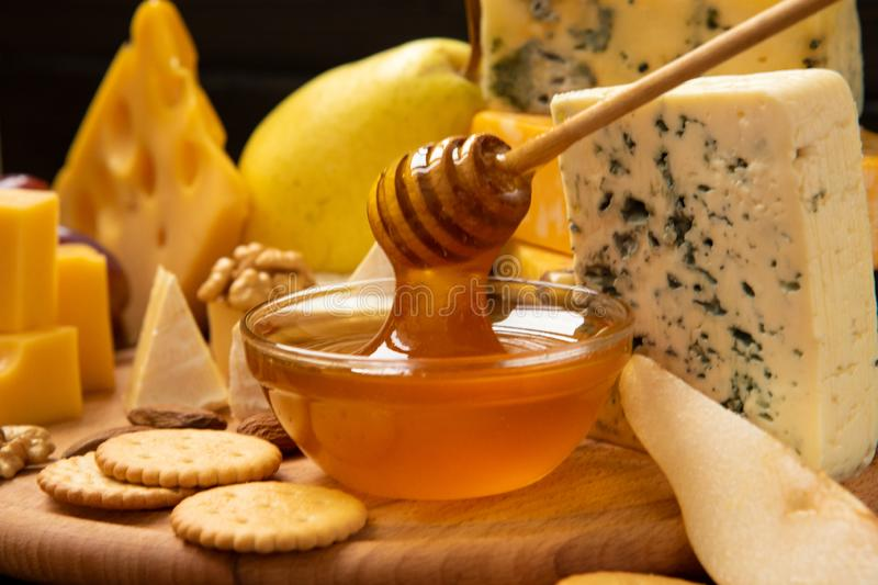 Assorted cheeses on a round wooden board royalty free stock photos