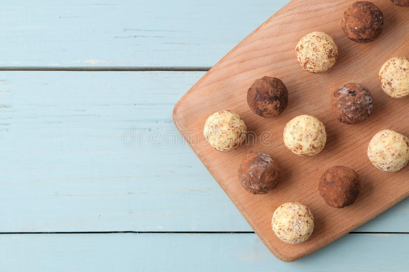 Assorted chocolates. Candy balls of different types of chocolate on a wooden board on a blue wooden table. top view stock photography