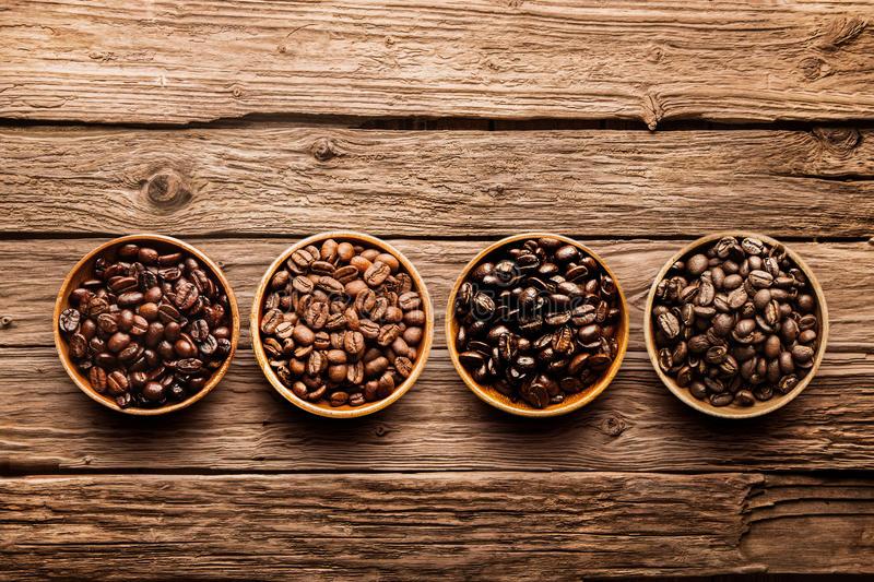 Assorted coffee beans on a driftwood background. Assorted raw and roasted coffee beans in small individual containers on a rustic, weathered textured driftwood royalty free stock image