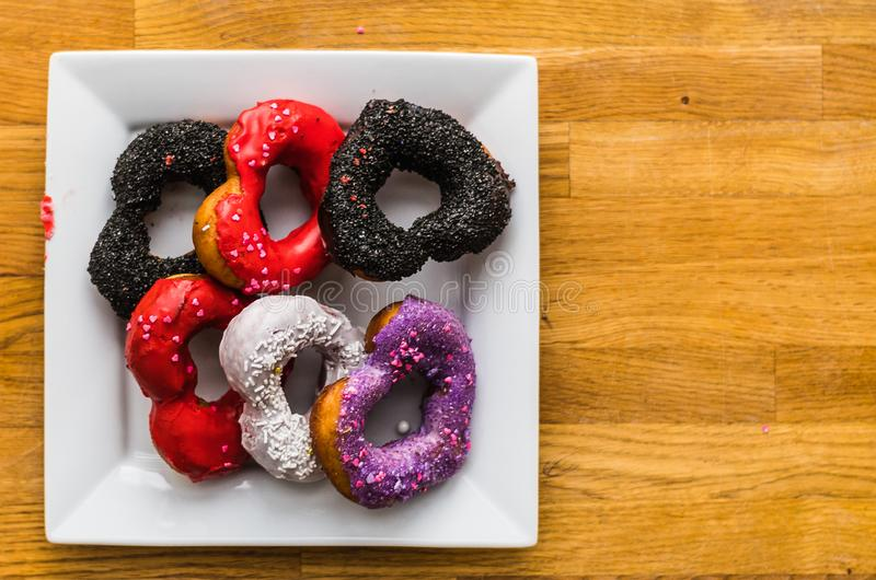 Valentines Day Donuts Full of Color. Assorted color and shapes of delicious donuts on a tray for Valentine`s Day stock photo
